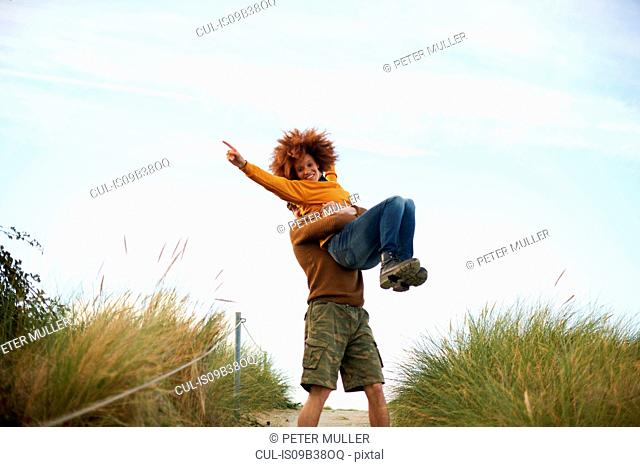 Couple playing on grassy dune