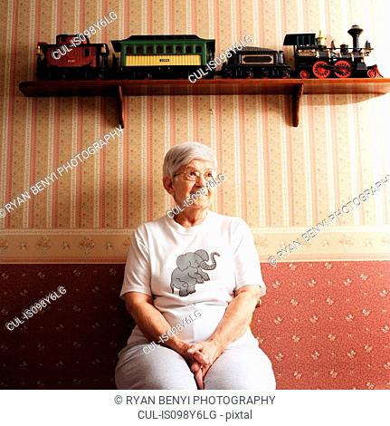 Portrait of senior woman with train set on shelf