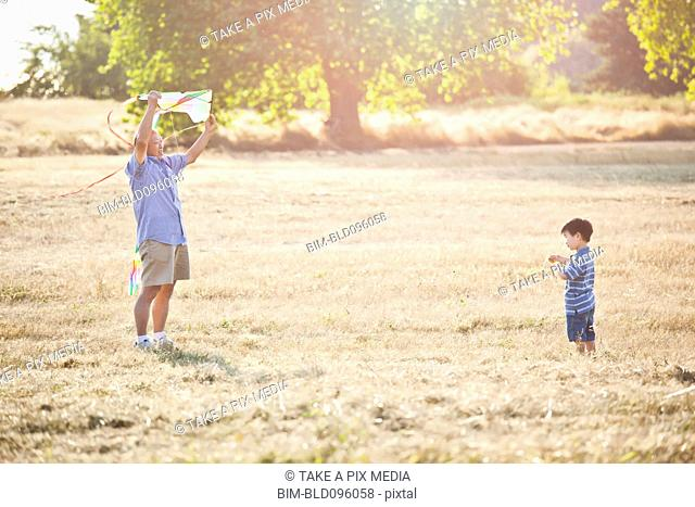 Chinese grandfather and grandson flying kite