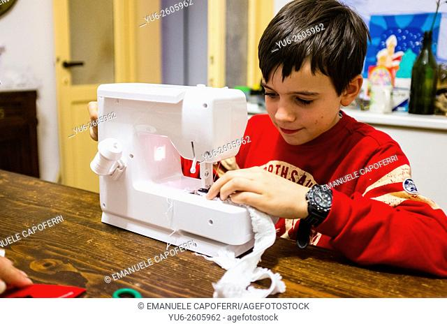 Child sewing with sewing machine at home
