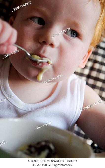 A baby feeding himself in a high chair, using a spoon
