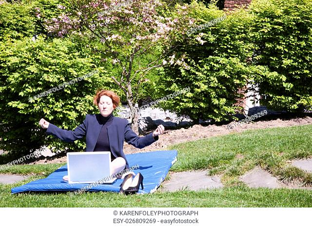 Professional woman in business suit on a yoga mat outdoors in front of computer