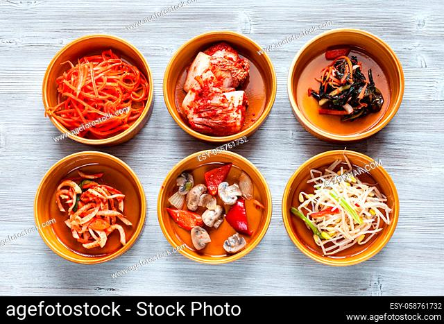 korean cuisine - top view of various side dishes (Banchan or Panchan) in ceramic bowls on gray table