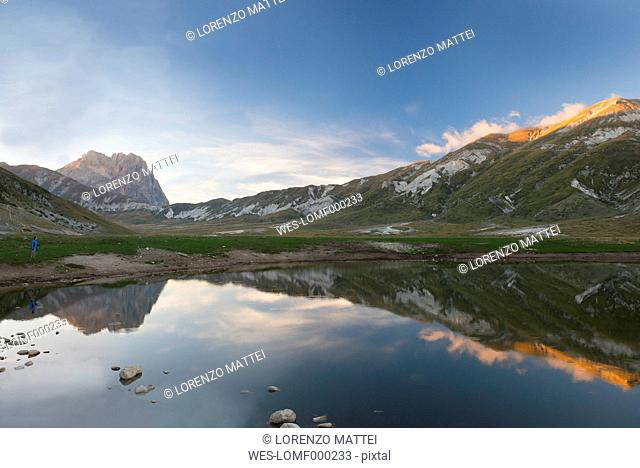 Italy, Abruzzo, Gran Sasso e Monti della Laga National Park, plateau Campo Imperatore, Corno Grande peak reflected in lake Petranzoni at sunset