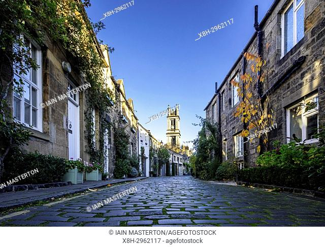View along traditional row of mews houses towards St Stephen's Church in Circus Lane in Stockbridge district of New Town in Edinburgh, Scotland, United Kingdom