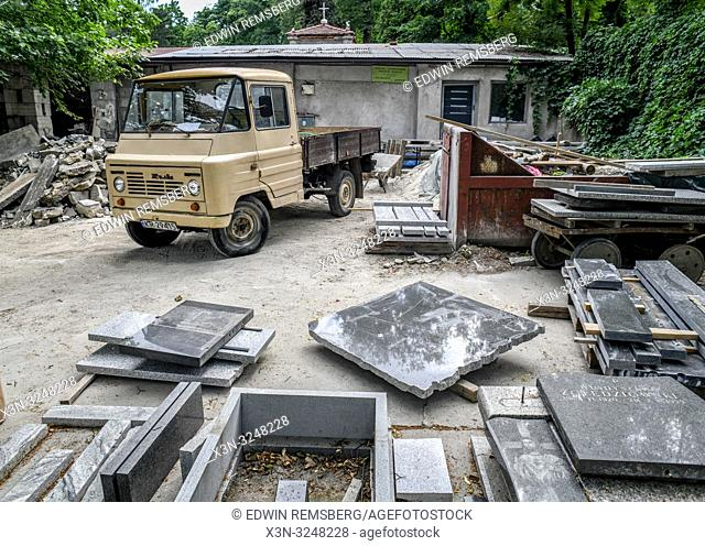 Work truck sits parked amongst scraps of stone used to make tombstones, Krak—w, Lesser Poland Voivodeship, Poland