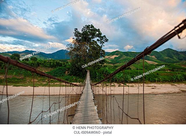 Diminishing perspective of wire bridge over river, Gia Lai Province, Vietnam