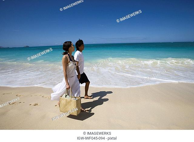 Profile of a young couple walking on beach