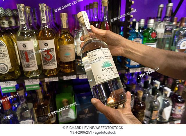 A discerning consumer chooses a bottle of Casamigos ultra-premium tequila in a liquor store in New York