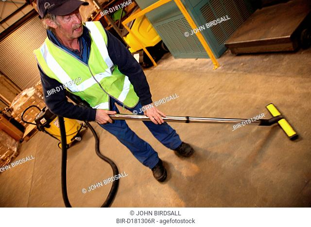 Man with a mild learning disability working as a factory cleaner, shown here hoovering, helped into employment by the Ready 4 Work team