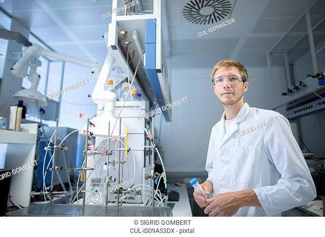 Portrait of young male scientist holding sample bottle in lab