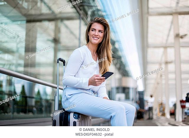 Smiling young businesswoman sitting on luggage with cell phone looking around