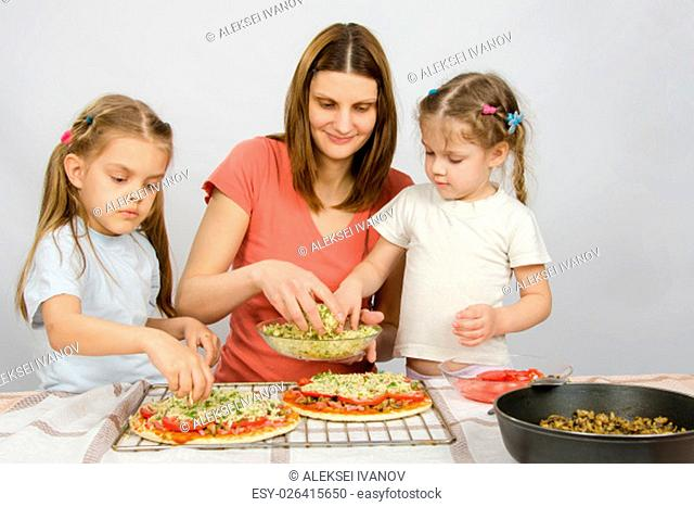 Mom with two young assistants make pizza
