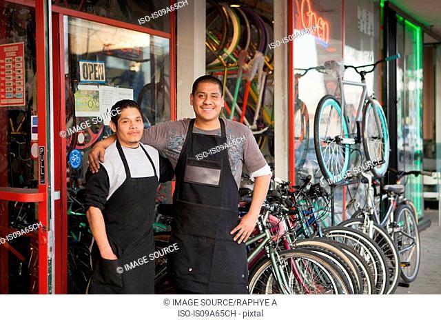 Mechanics smiling outside bicycle shop