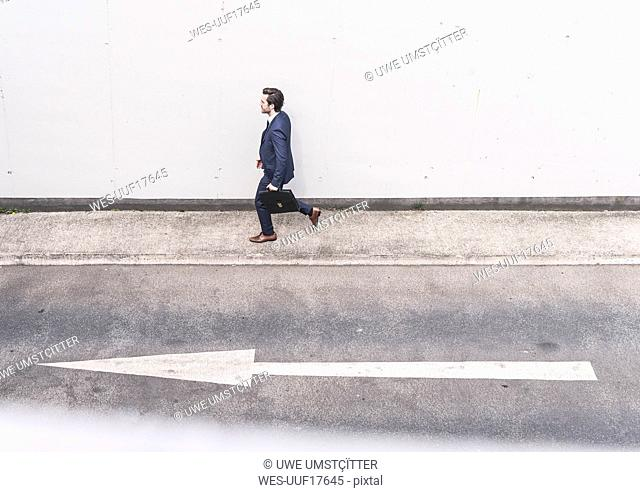 Businessman walking at road with arrow sign