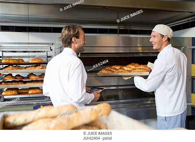 Baker holding bread in bakery kitchen with business owner