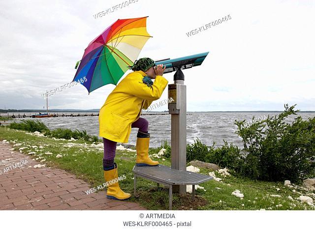 Germany, Steinhuder Meer, woman wearing yellow Wellington boots and rain coat looking through telescope