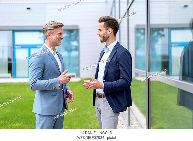 Two smiling businessmen talking outside office building