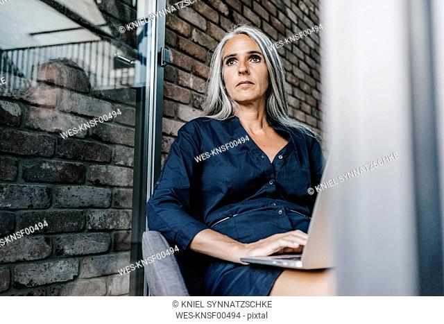 Woman with long grey hair using laptop