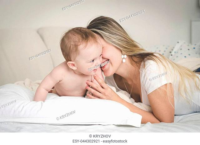 Portrait of laughing young mother with her 9 months old baby son on bed in bedroom
