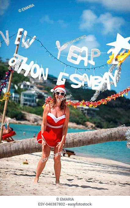 Cute joyful woman jumps in red dress and santa hat on exotic tropical beach. Holiday concept for New Years Cards. Koh Samui