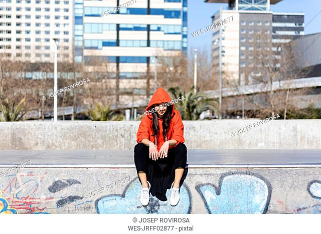Young contemporary dancer wearing red hoodie shirt, sitting on the floor with city in the background