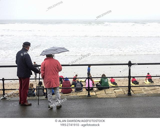 Elderly couple watching surf lesson in the rain at Saltburn by the sea, North Yorkshire, England, United Kingdom