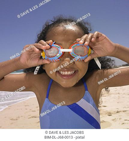 Smiling girl wearing goggles at beach