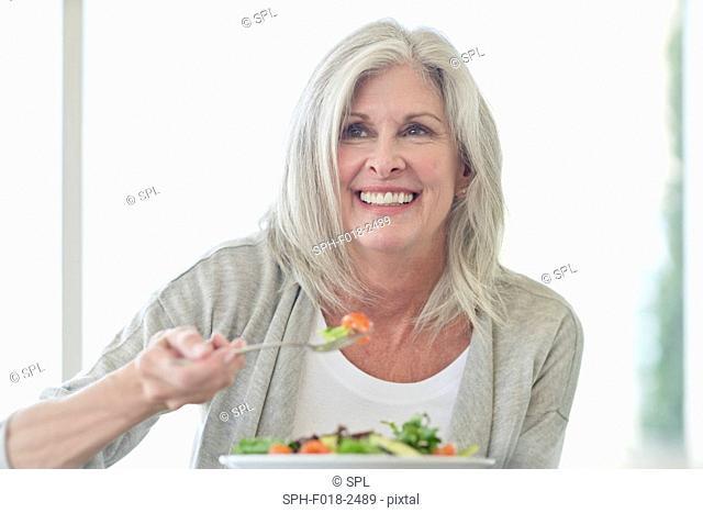 Senior woman eating salad, smiling