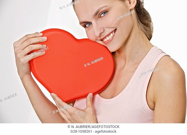 young smiling woman holding a red heart in front of her