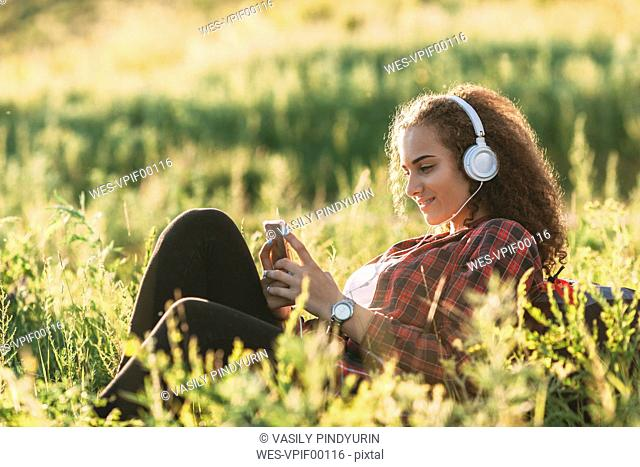 Teenage girl listening music with headphones on a meadow looking at cell phone