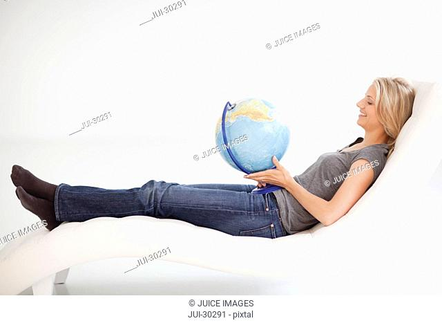 Mid adult woman holding world globe