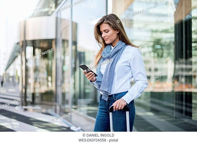 Young businesswoman with suitcase looking at smartphone