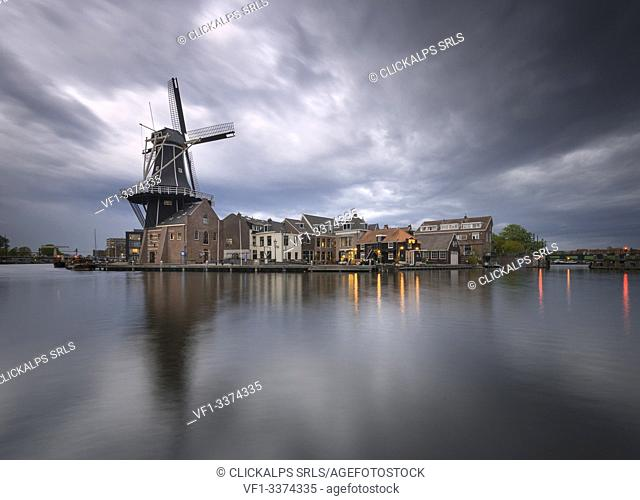 View of Windmill De Adriaan reflected in the canal of the river Spaarne during golden storm, Haarlem, Amsterdam district, Papentorenvest, Randstad