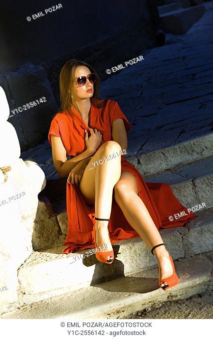 Woman exposing legs under long dress