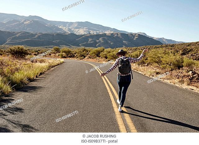 Woman walking along road markings of desert road, rear view, Sedona, Arizona, USA