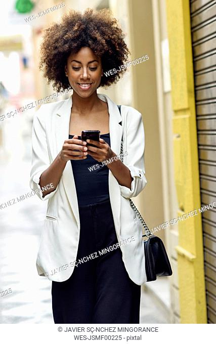 Portrait of smiling young woman with curly hair looking at cell phone