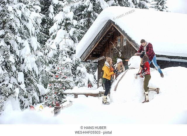 Austria, Altenmarkt-Zauchensee, friends building up big snowman at wooden house