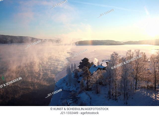 Clouds of steam rise over a freezing river on a very cold winter day in Sweden
