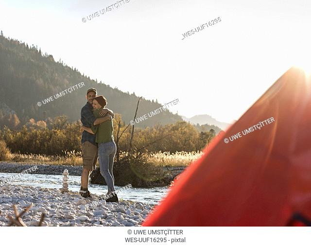 Mature couple camping at riverside in the evening light
