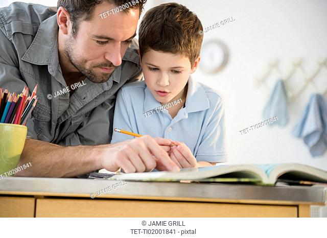 Father helping his son (8-9) with homework