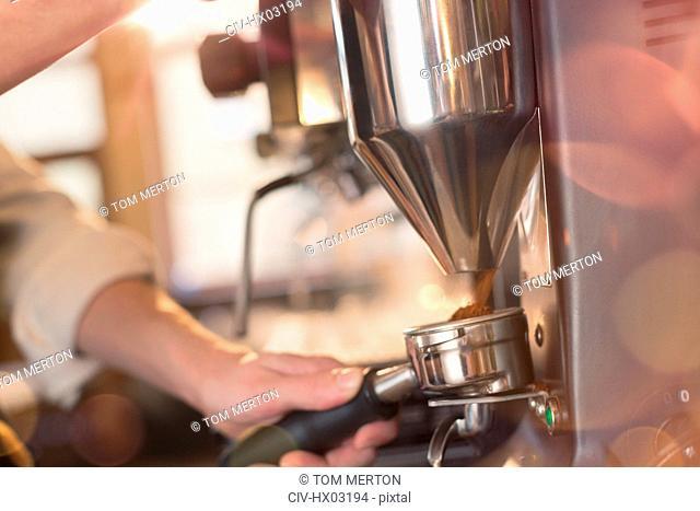 Close up barista using espresso machine grinder in cafe