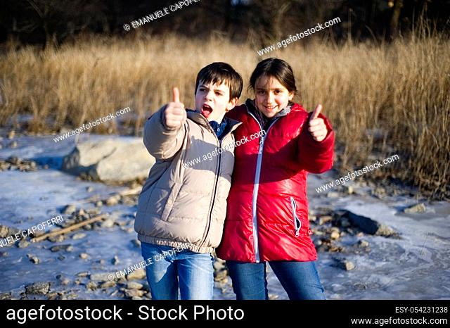 Children, siglings, portrait at the beach of the lake in winter, Lake Maggiore, Ispra, Italy
