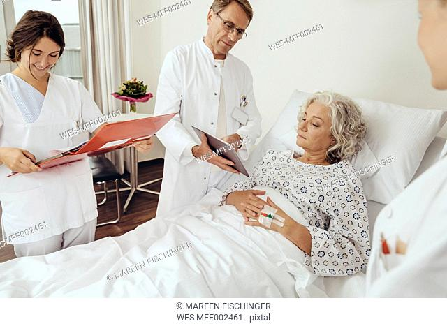 Senior woman in hospital with doctors at her bed doing their ward round