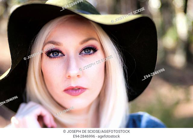 Portrait of a 30 year old blond woman looking at the camera wearing a floppy hat, outdoors