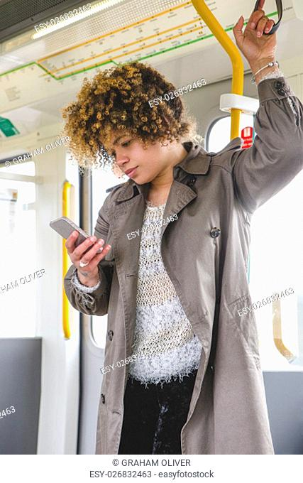 Woman standing on the train with a smart phone in her hand. She is holding the hand rail and looking down at her phone