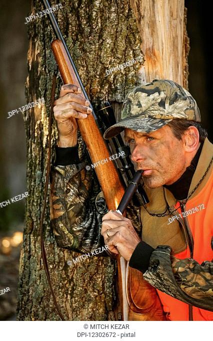 Deer Hunter Holding Rifle And Calling Deer