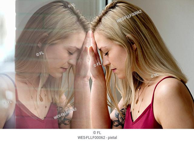 Profile of blond young woman and her reflection on windowpane