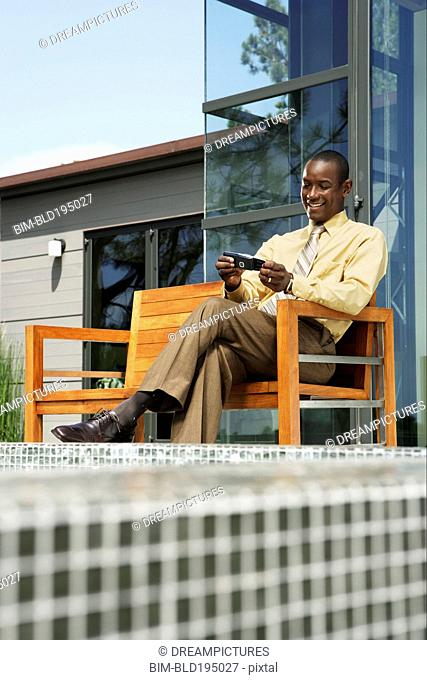 African American man text messaging on cell phone by swimming pool