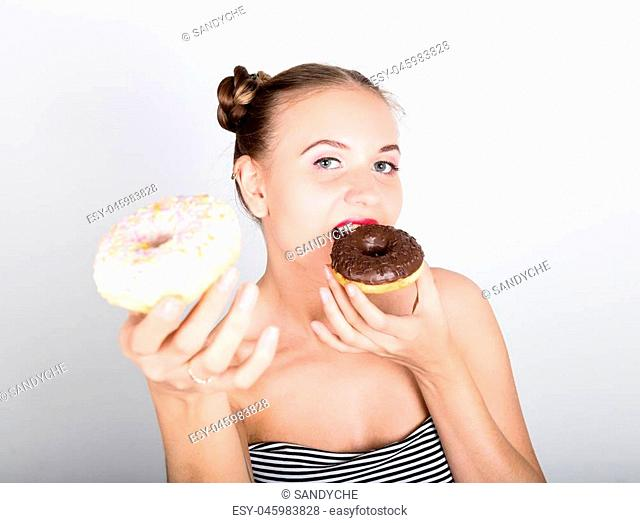young woman in bright makeup eating a tasty donut with icing. Funny joyful woman with sweets, dessert. dieting concept. junk food